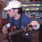 Intonation -- Adam Meyer, a fine luthier, is checking out the intonation before handing off the bass to John Brown for the final inspection.